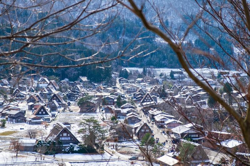 The sloped-roof and thatched-roof houses of snow cover and started to melt with a view of the branches in the foreground. At Shirakawa-go, Japan royalty free stock photography