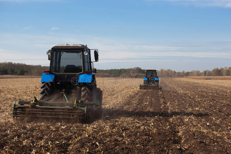 The sloping field. Two large blue traktor plow plowed land after harvesting the maize crop royalty free stock photography