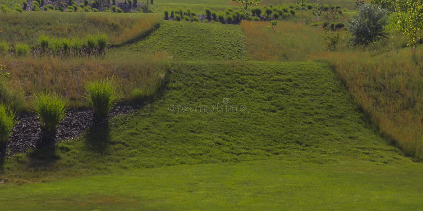 Sloping grassy terrain in Daybreak on a sunny day. View of a sloping grassy terrain in Daybreak, Utah on a bright sunny day. Beautiful manicured lawn with royalty free stock image