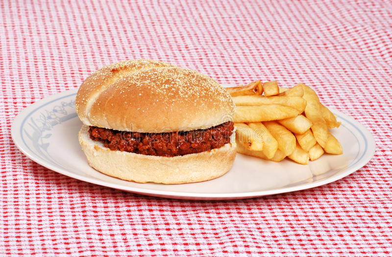 Sloppy Joe With French Fries. On plate with red and white checkered tablecloth stock photo
