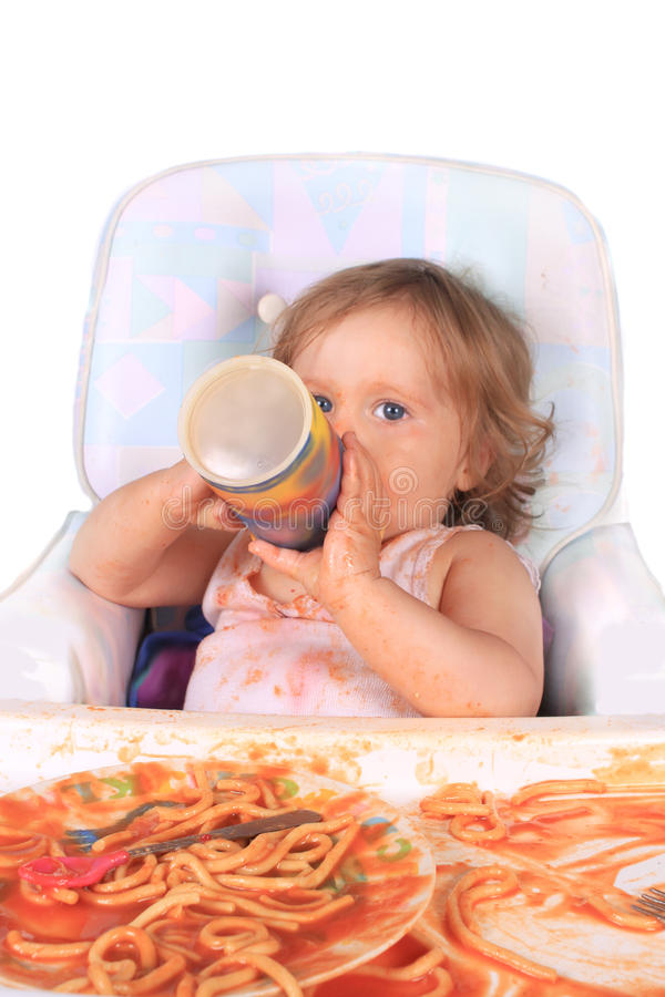 Slordig babymeisje het drinken sap dat spaghetti eet stock afbeeldingen