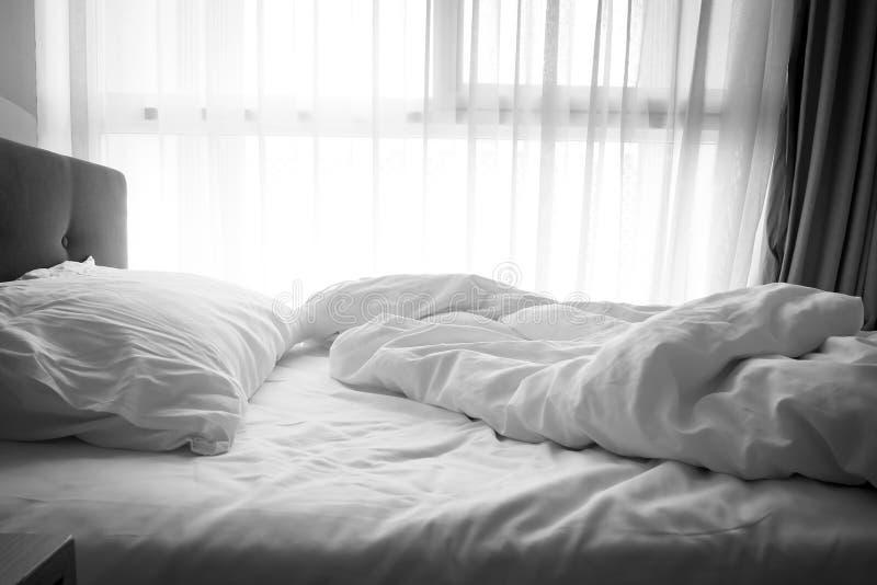 Slordig Bed Wit hoofdkussen met deken op onopgemaakt bed stock foto