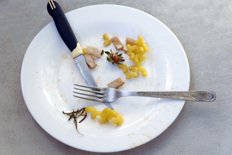 Slordig voedselafval na een maaltijd met een mes en een vork stock foto's