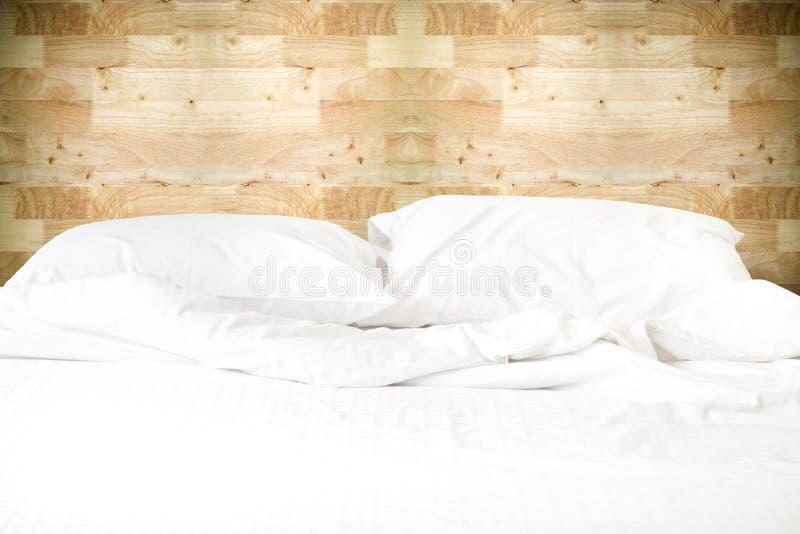 Slordig wit bed met hoofdkussen en deken op houten muur backgroun royalty-vrije stock fotografie