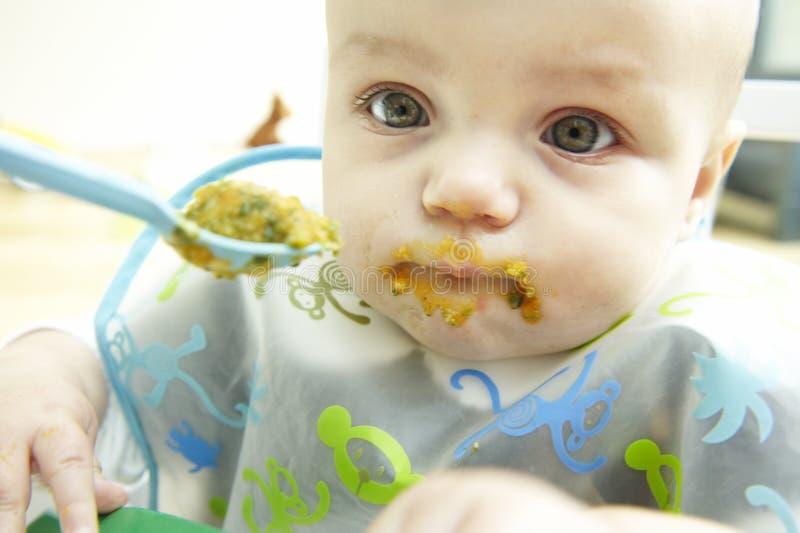 Slordige Baby die wordt gevoed stock afbeelding