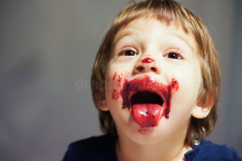 Slordige jongen die rood bloedig roomijs eten stock fotografie