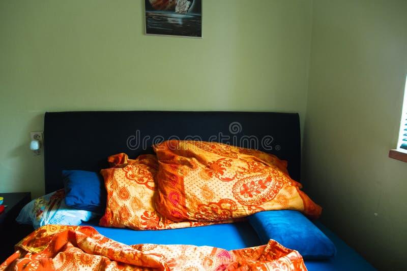 Slordige slaapkamer met bed linens stock fotografie