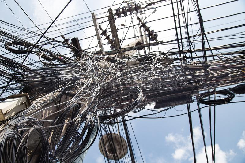 Slordige verwarde elektriciteit, telecommunicatiedraden, kabels binnen stock afbeeldingen