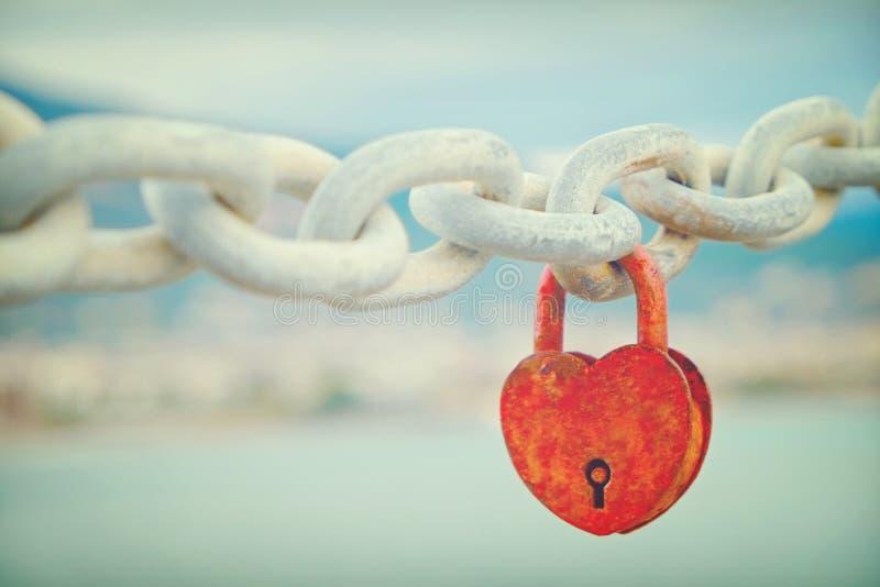 Slot in de vorm van hart het hangen op ketting over de overzeese meningsachtergrond stock foto