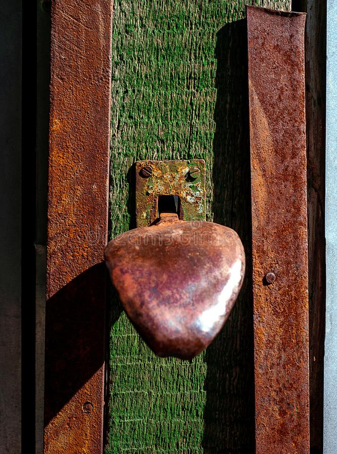 Slot en handvat op houten groene deur met gebarsten en kras Verticale grungetextuur royalty-vrije stock afbeelding