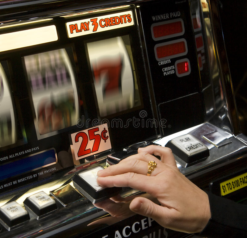 Slot machine. Woman's hand hits stop on slot machine in casino stock photography