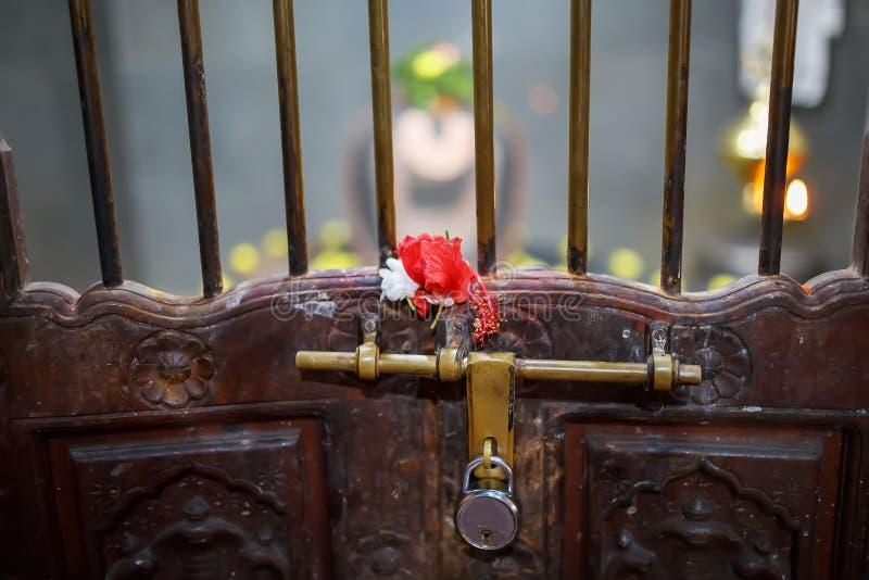 Slot op de oude deur van de Indische tempel met een rooster en een bout Rode bloem op het rooster royalty-vrije stock afbeeldingen