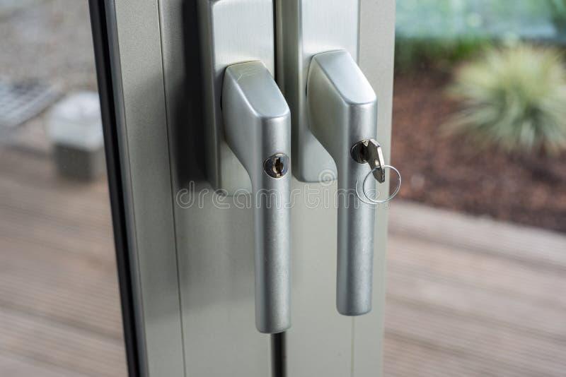 Sloten bij glasdeuren aan de tuin als defensie voor inbraak stock afbeeldingen