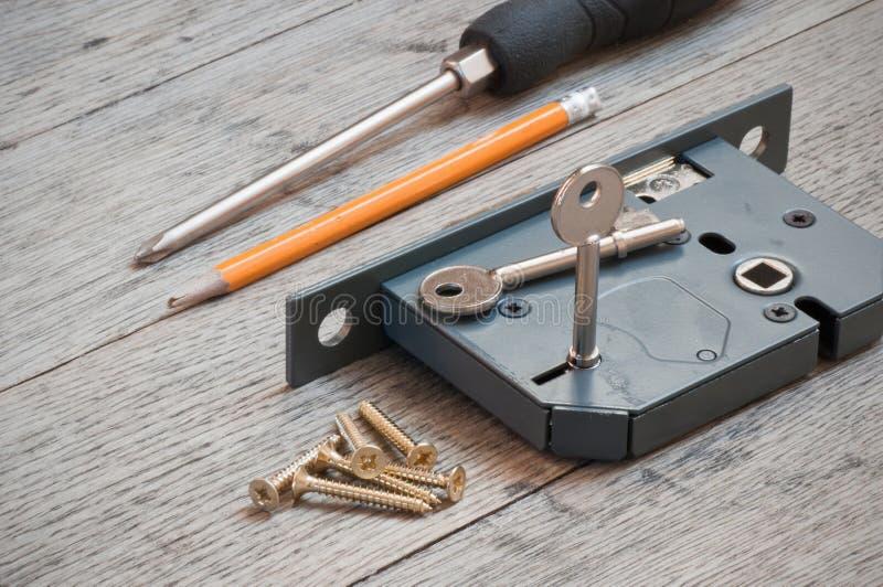 Slotenmakerhulpmiddelen en nieuw slot klaar om op een huisdeur worden gepast stock foto