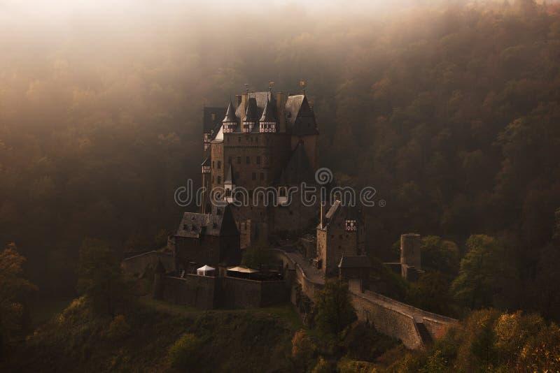 Slott för småstadEltz saga i dimman royaltyfri foto