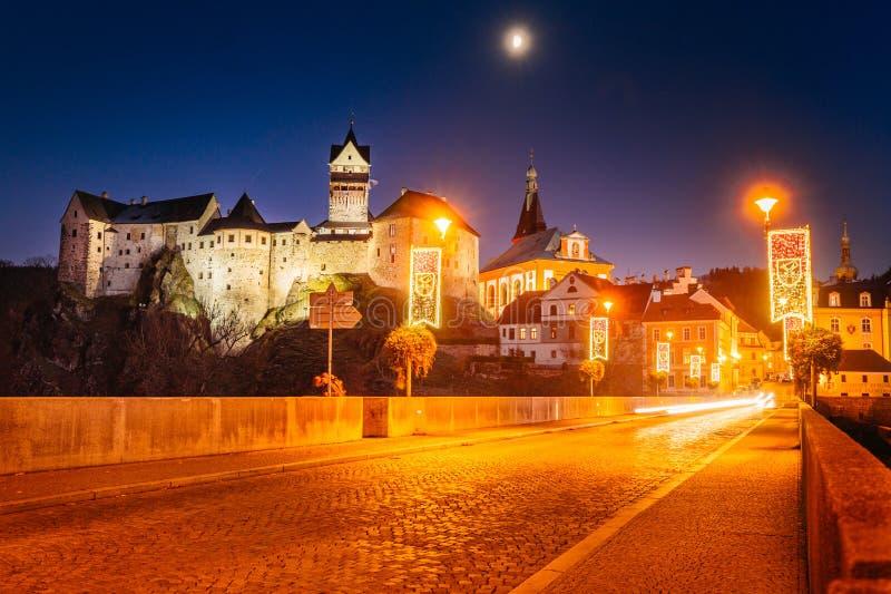 Slott Loket i vinter, lång nattexponering med härlig blå himmel och gula ljus för gatajulstad med sikt på floden arkivbilder