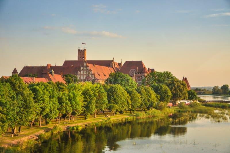 Slotten av den Teutonic beställningen i Malbork, Polen med den Nogat flodkusten århundradeslotten för th 13 är den största slotte royaltyfria bilder