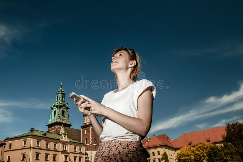 slottkrakow wawel En ung kvinna med en mobiltelefon i borggården av en forntida slott Ta bilder vid telefonen Nålar arkivbild
