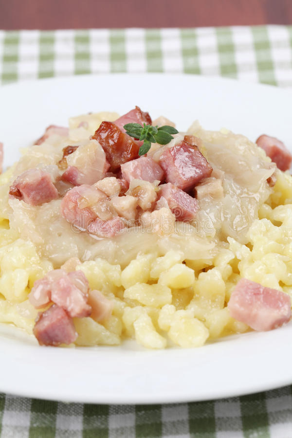 Slovak national food - Halushky. Slovak national food called halusky - small potato dumplings (gnocchi) with sauerkraut and smoked meat royalty free stock photos
