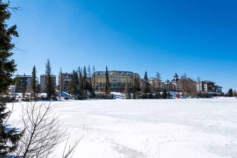 Slovakia: Strbske pleso resort, view of frozen lake in winter and hotel resort above. Blue sky. stock photo