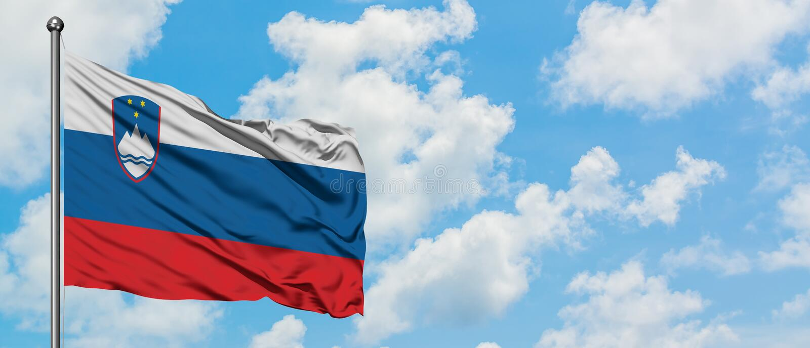 Slovenia flag waving in the wind against white cloudy blue sky. Diplomacy concept, international relations.  royalty free stock photo