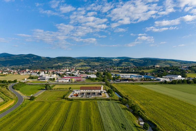 Sewage treatment plant in rural area, small town and mountains in background royalty free stock photography
