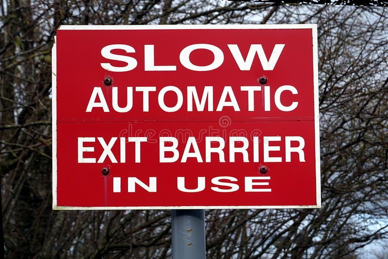 Slow automatic exit barrier in use sign stock photography