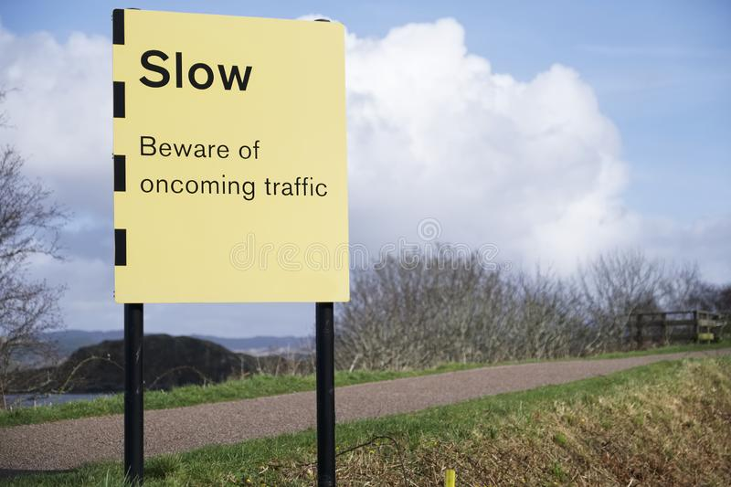Slow beware of oncoming traffic sign road safety stock photo