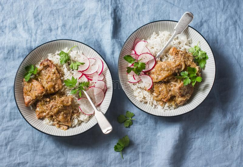 Slow cooker pork tenderloin with rice pilaf and radish salad on a blue background, top view. stock photo