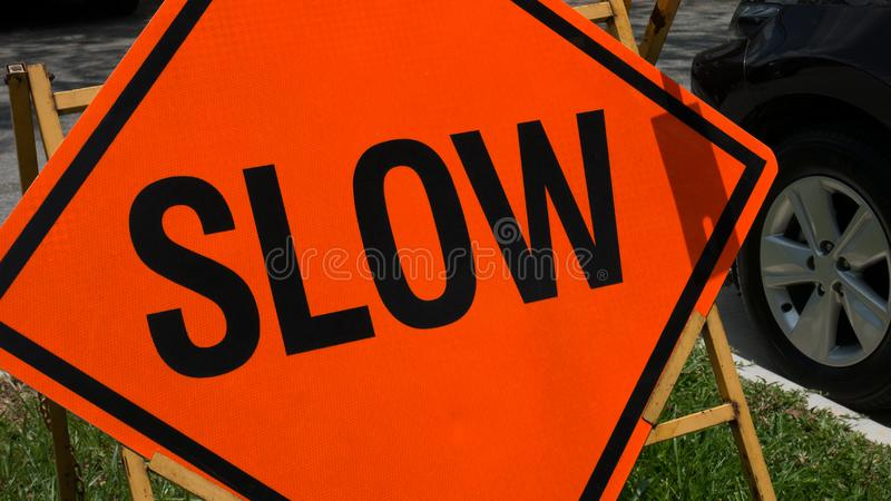 Slow down red banner traffic sign on the road with car in background. royalty free stock image