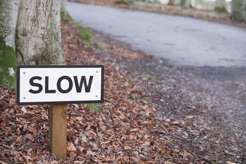 Slow down road safety sign on rural countryside highway uk stock photography