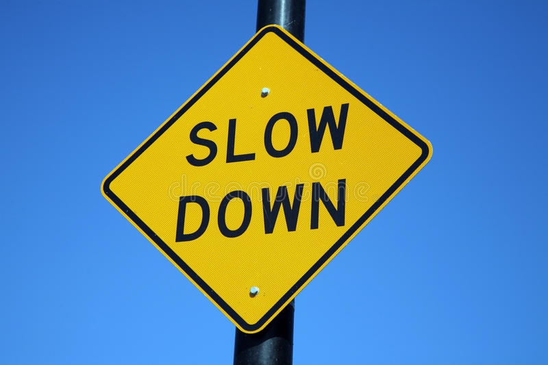 Slow down sign. Signage on a pole that says to slow down