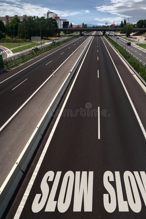 Slow down sign. Double SLOW sign on a city highway royalty free stock images