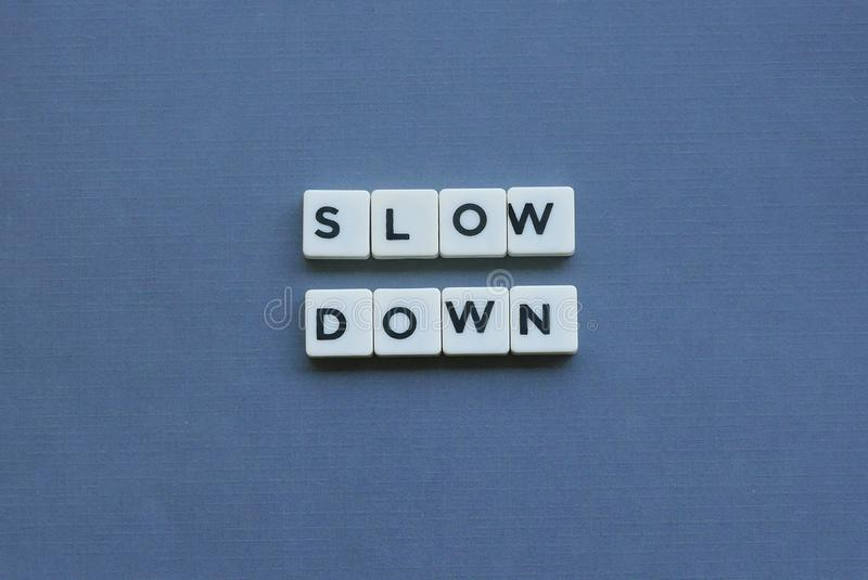 ' Slow Down ' word made of square letter word on grey background. Traffic, warning, road, safety, caution, speed, transportation, travel, drive stock photos
