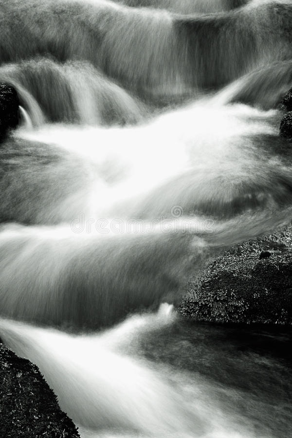 Slow motion blur waterfall. Background of waterfall cascading over rocks with slow motion blur stock photos