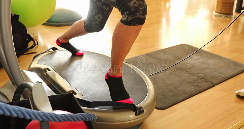 Vibration plate thigh toner. Slow motion half body of fit woman warming up in short leggings, training legs with thigh toner on the step. Modern gym defocused stock photos