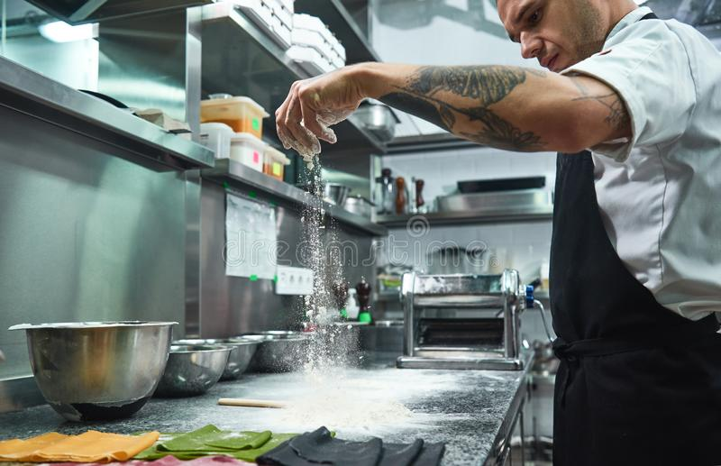 Slow motion. Handsome young chef with black tattoos on his arms pouring flour on kitchen table before making pasta stock photography