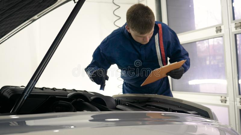 Slow Motion Man Male professional in working uniform and flashlight folder in his hands checks the car from all sides for servic. Eability Concept of: Car center royalty free stock photos