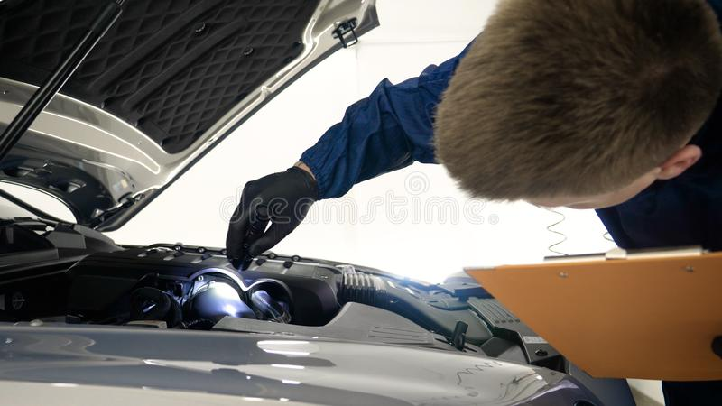 Slow Motion Man Male professional in working uniform and flashlight folder in his hands checks the car from all sides for servic. Eability Concept of: Car center royalty free stock photography