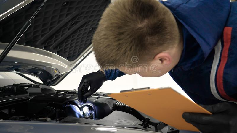 Slow Motion Man Male professional in working uniform and flashlight folder in his hands checks the car from all sides for servic. Eability Concept of: Car center royalty free stock images