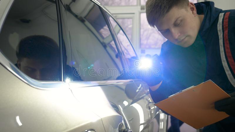 Slow Motion Man Male professional in working uniform and flashlight folder in his hands checks the car from all sides for servic. Eability Concept of: Car center stock photo
