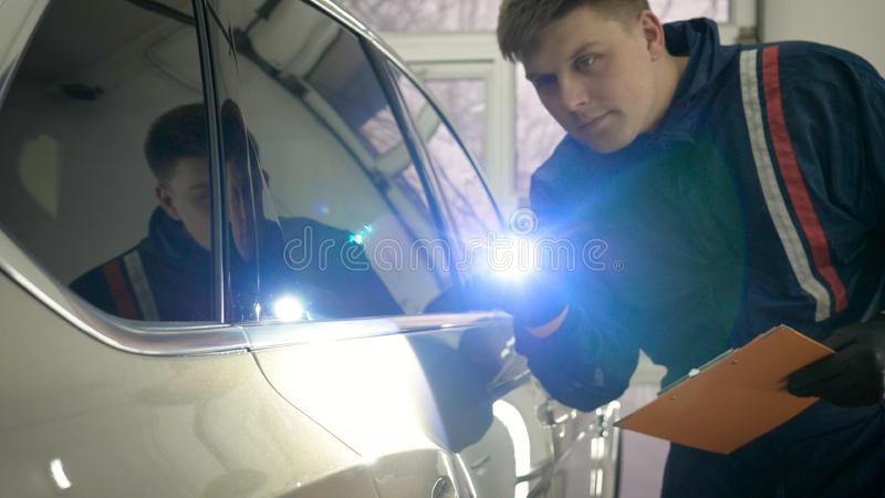 Slow Motion Man Male professional in working uniform and flashlight folder in his hands checks the car from all sides for servic. Eability Concept of: Car center stock image