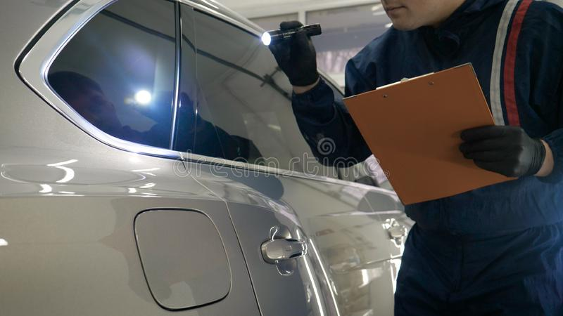Slow Motion Man Male professional in working uniform and flashlight folder in his hands checks the car from all sides for servic. Eability Concept of: Car center royalty free stock image