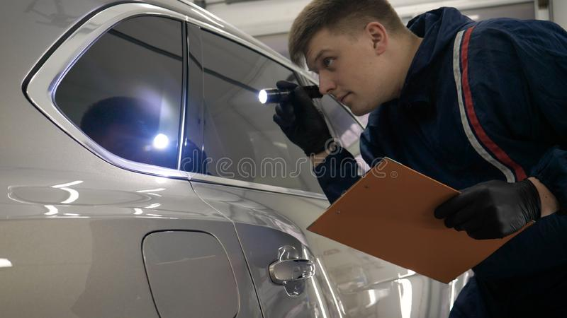 Slow Motion Man Male professional in working uniform and flashlight folder in his hands checks the car from all sides for servic. Eability Concept of: Car center stock images