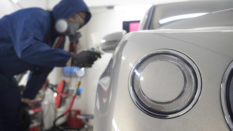 In slow motion, a Man Man professional in working uniform with spray guns in his hands and a respirator in protective glasses pu. Ts paint ceramics on the car on stock images
