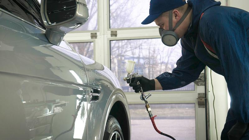 In slow motion, a Man Man professional in working uniform with spray guns in his hands and a respirator in protective glasses pu. Ts paint ceramics on the car on royalty free stock images