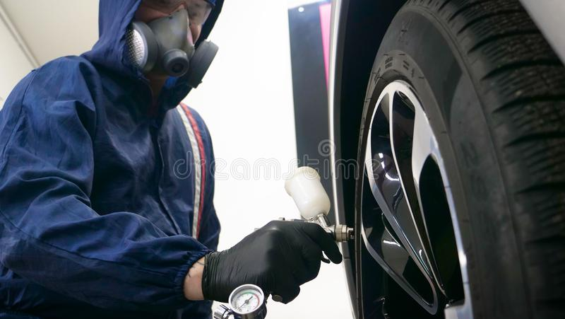 In slow motion, a Man Man professional in working uniform with spray guns in his hands and a respirator in protective glasses pu. Ts paint ceramics on the car on stock photo