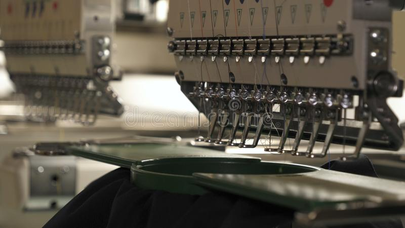 In slow motion video in a garment factory, a sewing machine embroiders various companies and engravings. Concept of: Automated wor. K, Sewing machine, Engraving stock image