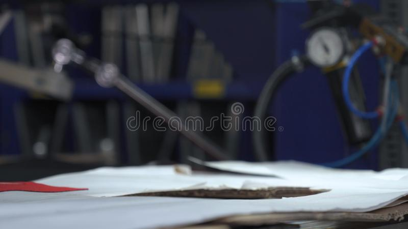 In a slow motion video in a garment factory, women press cut various pieces of clothing and fabric locks and various materials u. Sing different machines stock photos