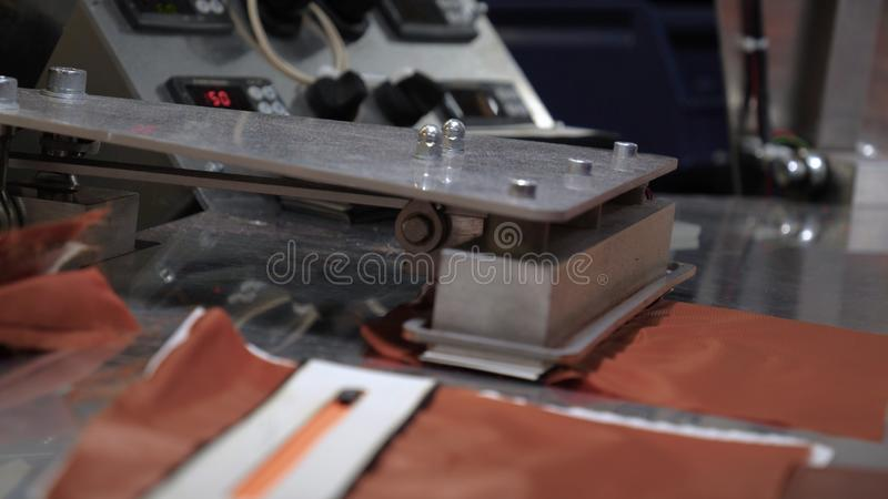 In a slow motion video in a garment factory, women press cut various pieces of clothing and fabric locks and various materials u. Sing different machines royalty free stock photo